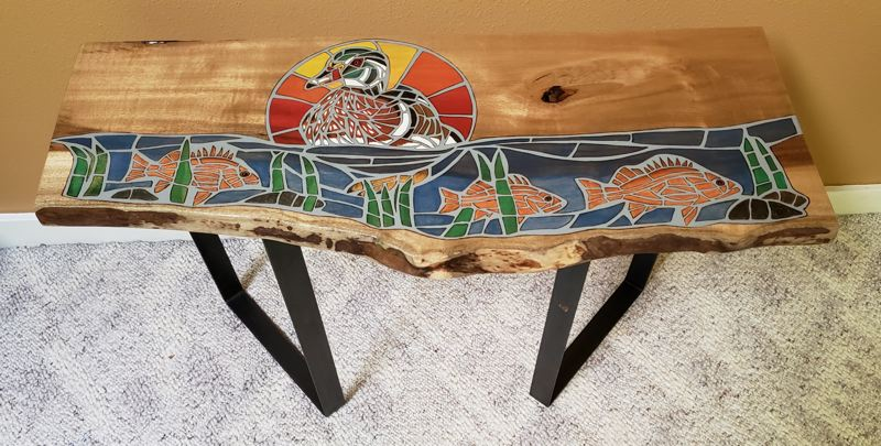 COURTESY PHOTO - This accent table featuring fish and ducks is one of Carol Pulvermacher's pieces in the Spiral Gallery's featured show for August.