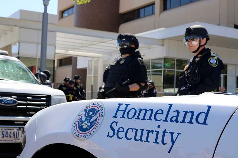 PMG FILE PHOTO: ZANE SPARLING - Federal police officers with the Department of Homeland Security stand guard outside an Immigration and Customs Enforcement facility in Southwest Portland in 2019.