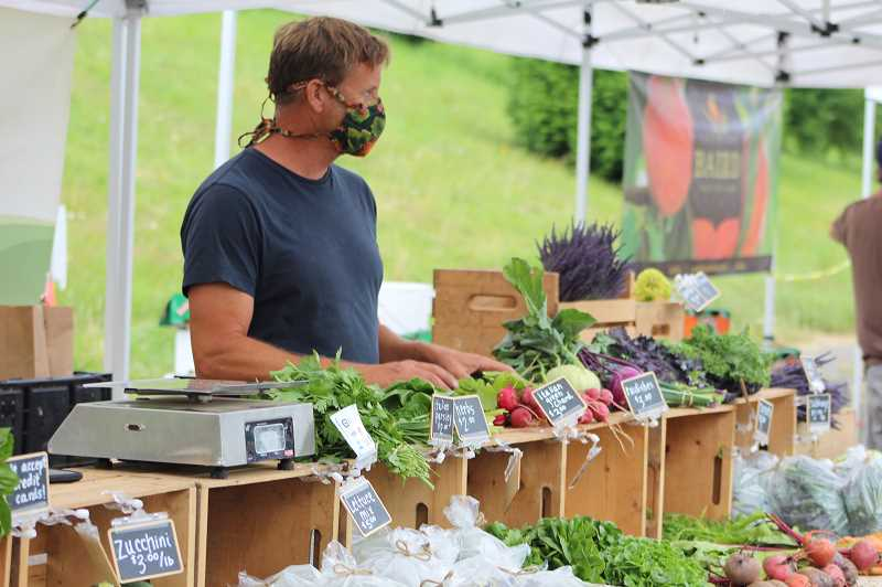 PMG PHOTO: COURTNEY VAUGHN - Peter Weber of Barn Frog Farm gathers produce for a customer at the Hillsdale Farmers' Market. Weber and other vendors say the weekly market affords shoppers distance, and fresh air.