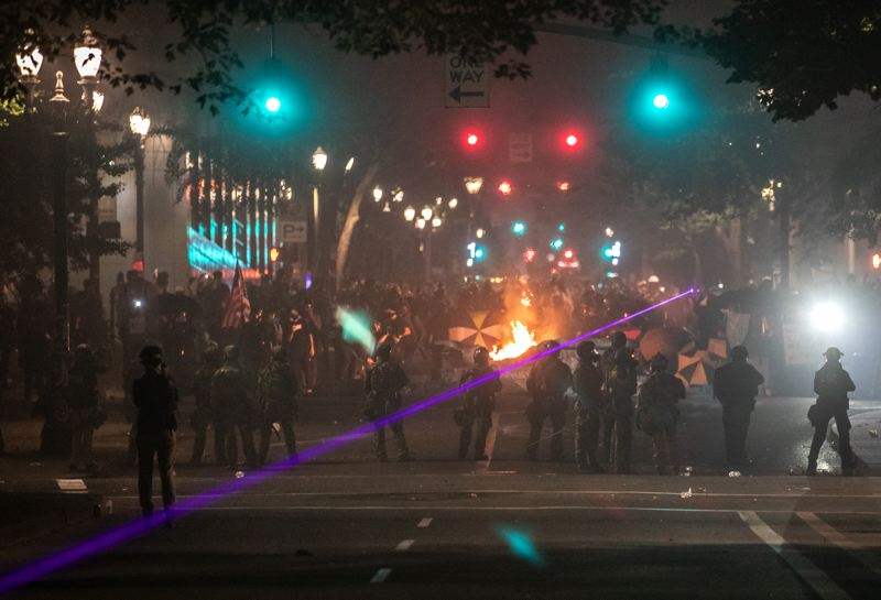 PMG PHOTO: JONATHAN HOUSE - A laser beam arcs across a line of federal officers facing off with a crowd of protesters during a recent downtown Portland protest.