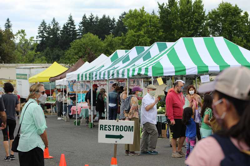 PMG PHOTO: COURTNEY VAUGHN - Shoppers peruse booths at the Hillsdale Farmers Market in July. The market is open, but masks are required at all times and capacity is limited to 65 people.