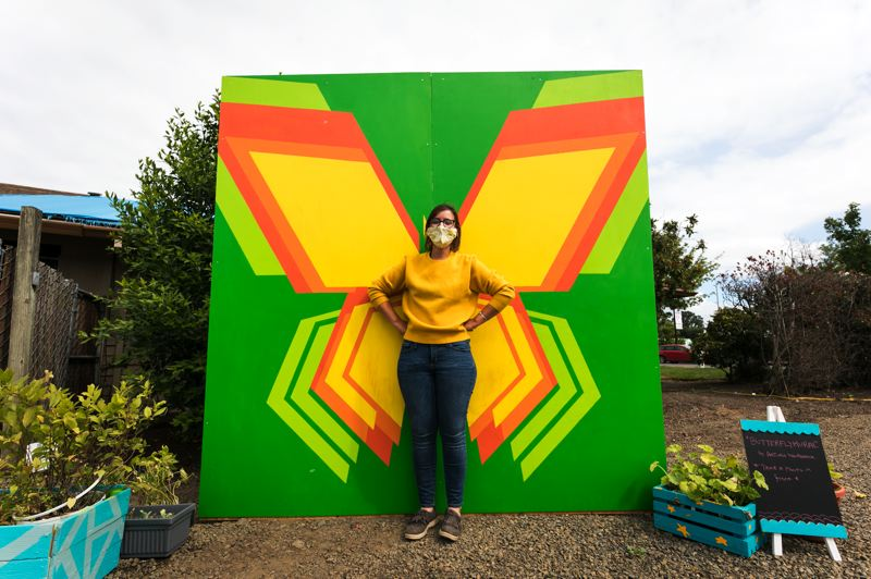 PMG PHOTO: JAIME VALDEZ - Sarah Birkle, who headed a project to create a 'pop-up plaza' in Cornelius, stands in front of a mural by local artist Arturo Villasenor located at the pop-up plaza.