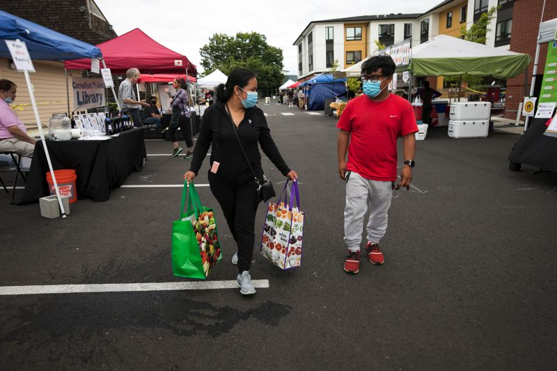 PMG PHOTO: JAIME VALDEZ - Patricia Reyes, left, and her son, Victor Montano, 19, leave the Cornelius Farmers Market with full bags from the new farmer's market in Cornelius.