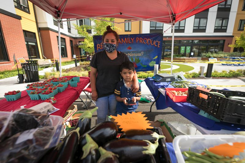PMG PHOTO: JAIME VALDEZ - Margarita Reyes and her son stand at the Reyes Family Produce booth at the new Cornelius Farmers Market.