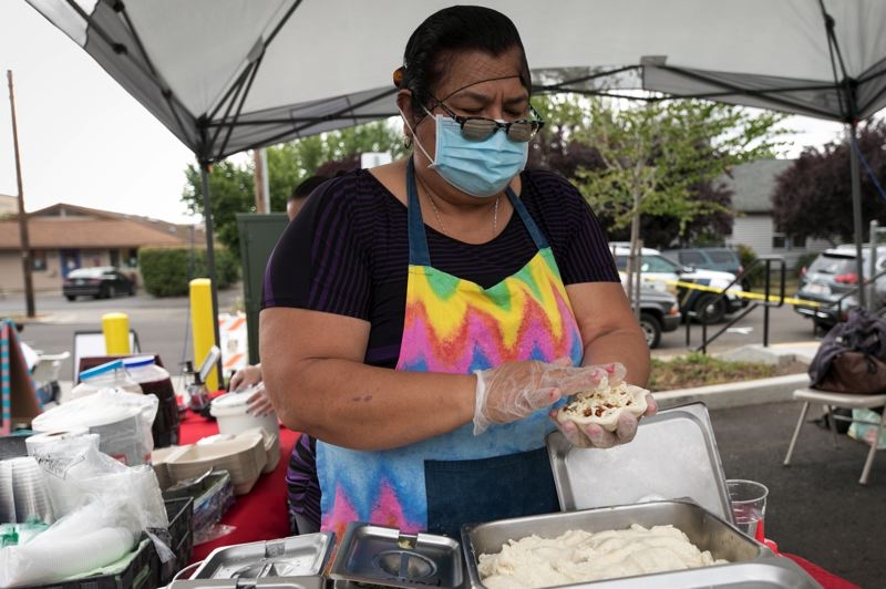 PMG PHOTO: JAIME VALDEZ - Guadalupe Maldonado makes a pupusa for a customer at her booth at the Cornelius Farmers Market.
