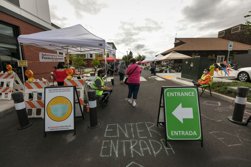PMG PHOTO: JAIME VALDEZ - Folks make their way through the entrance of the Cornelius Farmers Market.