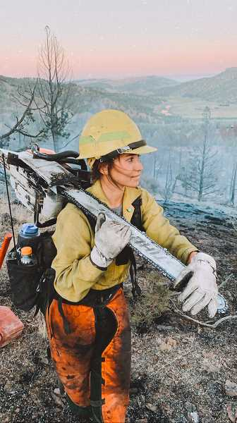 PHOTO CONTRIBUTED BY DAKOTA STEEN - Lacy Camara, a Forest Service Firefighter, has an expression of exhaustion and emotion as she pauses with her chainsaw and assesses  the landscape near the Wickiup Road Fire west of Post. The fire was reported on Saturday, July 25.