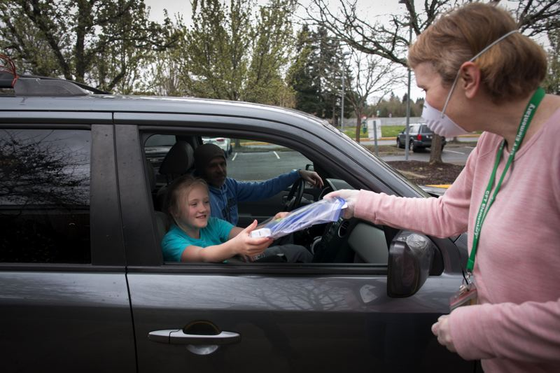 PMG PHOTO: JAIME VALDEZ - A student picks up an iPad from school staff during a device pick-up day for students at Charles F. Tigard Elementary School in April.
