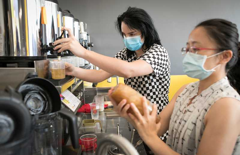 PMG PHOTO: JAIME VALDEZ - Kendra Webb, left, and Tiffany Chang make teas at Happy Lemon Tea. Chang is in town to help train staff at the tea business before it opens on Wednesday at Bridgeport Village.