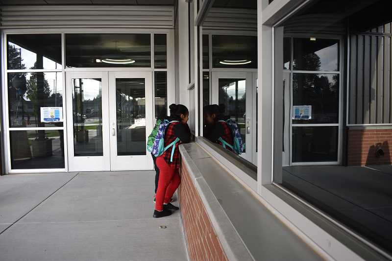 PMG PHOTO: TERESA CARSON - A student peers in the window of North Gresham Elementary at the start of the 2019 school year. Students will start the 2020-21 school year online.