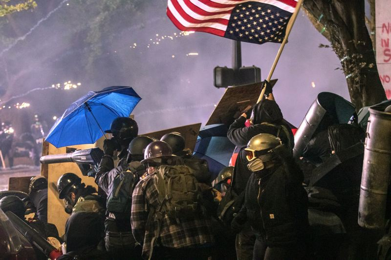 JONATHAN HOUSE - Protesters hide behind a shield wall as federal agents fire crowd control munitions down SW Salmon Street after a rally on July 25 turned unruly.