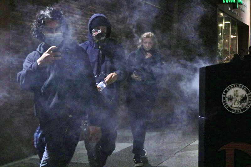 PMG PHOTO: ZANE SPARLING - Protesters walk past a burning trash can in downtown Portland during a recent demonstration.