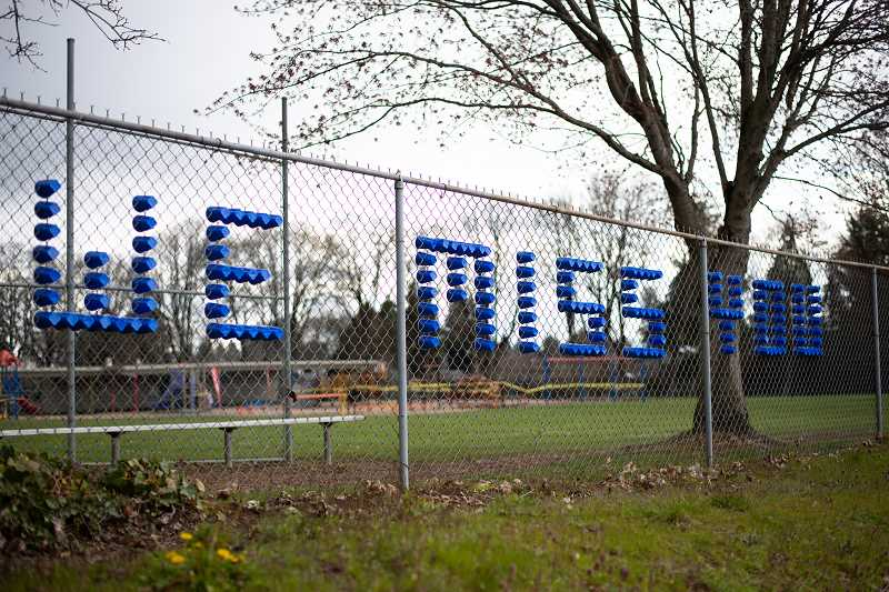 PMG PHOTO: ANNA DEL SAVIO - Plastic cups inserted into the chain-link fence outside a Scappoose school spelled out 'we miss you' earlier this year when schools were shuttered to slow the spread of COVID-19.