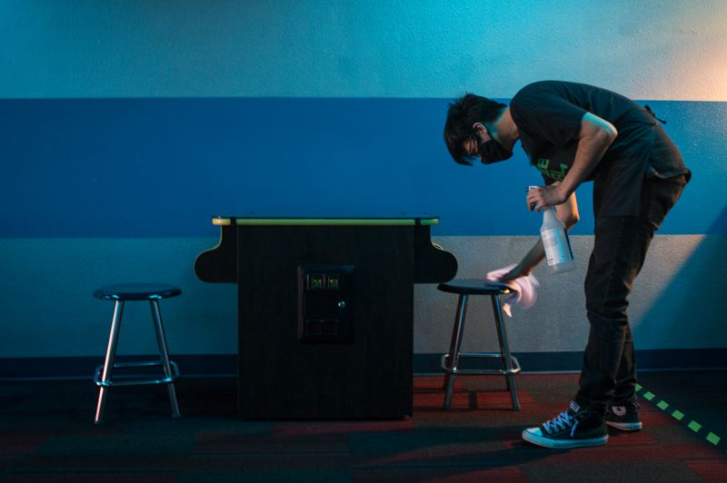 PMG PHOTO: JAIME VALDEZ - An employee at Hillsboro's new 80s-themed Arcade 2084 sanitizes a video game.