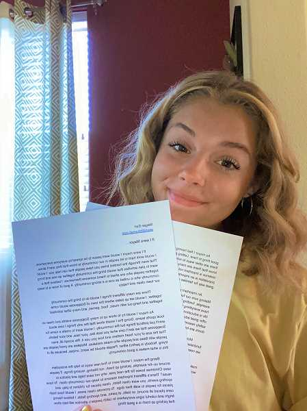 COURTESY OF MEGAN EARL - Megan Earl, winner of the Oregon Mayors Association 2020 'If I Were Mayor' contest, holds up a copy of her winning essay.