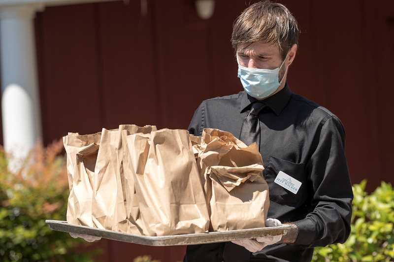 PMG PHOTO: JAIME VALDEZ - Jeff Walker, director of sales and outreach at Avamere at Sherwood, an assisted living and memory care facility, displays the sack lunches handed out to essential workers on July 31.