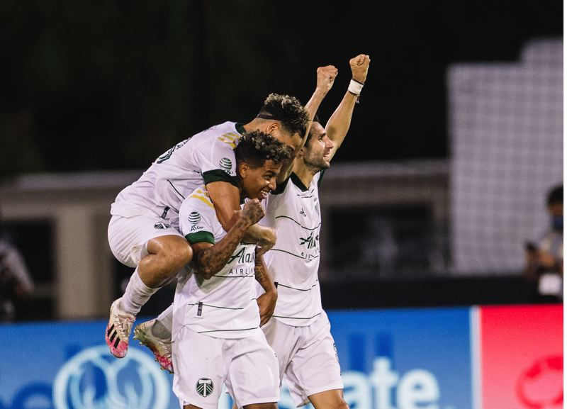 COURTESY PHOTO: MLS/JARED MARTINEZ AND MATTHEW STITH - Andy Polo i.s hugged by Pablo Bonilla as Diego Valeri celebrates Polo's goal Saturtday in Portland's 3-1 win over New York City FC at the MLS is Back Tournament.