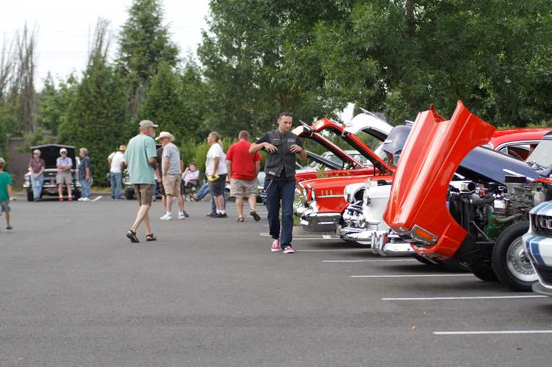 PMG PHOTO: WADE EVANSON - Onlookers checkout some of the cars on display at the Forest Grove Cruise-In Friday night, July 31, at the Walmart in Cornelius.