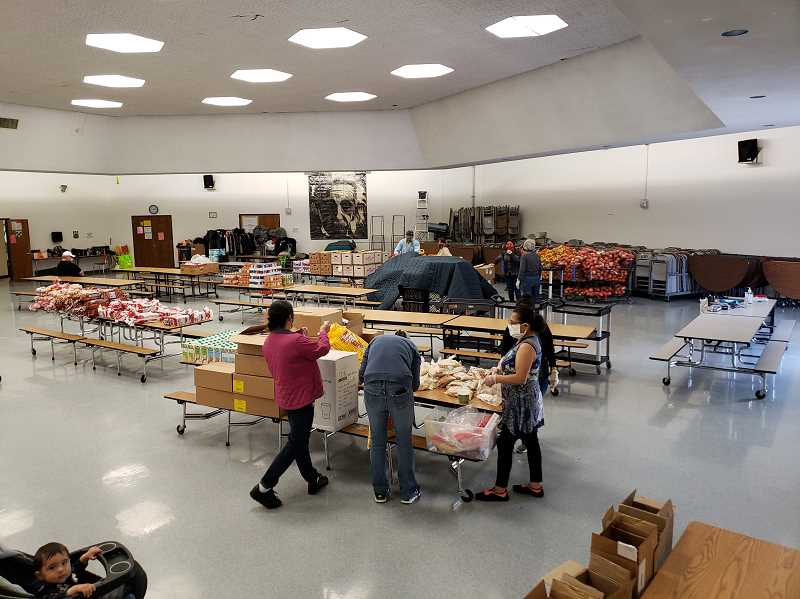 COURTESY PHOTO: MITCH TAYLOR - Volunteers at the Neil Armstrong Food Bank, including Susan Winterbourne (back right) of the Forest Grove Daybreak Rotary speaking with the Neil Armstrong Food Bank coordinator Elvira Josafat.