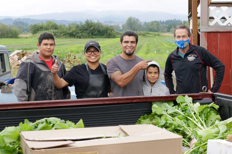 COURTESY PHOTO: JAMES MORRIS - Lilia and Cesar, and their sons, of Greenville Farms proudly load produce for Mitch Taylor and other Rotarians to deliver to the food bank at the Virginia Garcia Cornelius Wellness Center.