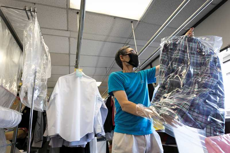 PMG PHOTO: JAIME VALDEZ - Oregon Dry Cleaners owner Harry Yu hangs up a shirt that was dry-cleaned at his business in Beaverton.