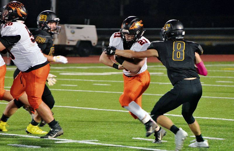 PMG FILE PHOTO - Scappoose's Deacon Smith tries to get away from St. Helens' Adam Stockwell in 2019. Now, both the Indians and Lions wonder if they'll play in 2020.