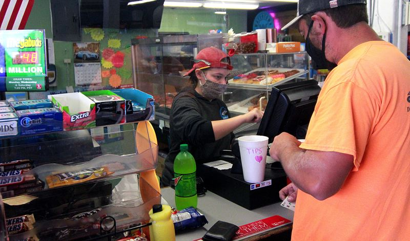 PMG PHOTO: MILES VANCE - Josie Head (left) serves a customer at Nelson's Neighborhood Market and Deli in Scappoose on Monday, Aug. 3.