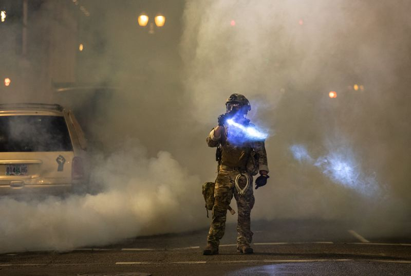 PMG PHOTO: JONATHAN HOUSE - A federal officer shines a flashlight as smoke billows through downtown Portland during a recent protest.