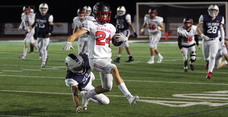PMG PHOTO: MILES VANCE - Nothing's for sure in the COVID-19 era, but scenes like this one is — Clackamas wide receiver Miles Williams looking for yards against Lake Oswego. Football may be back for 2020-21, but not until the springm based on a new OSAA sports calendar released Wednesday, Aug. 5.
