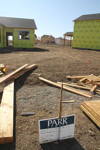 PMG PHOTO: JUSTIN MUCH - Construction workers keep busy erecting homes in Woodburns Boones Crossing Subdivision. New housing in anticipation of more housing needs is a significant part of Woodburns boom in building.