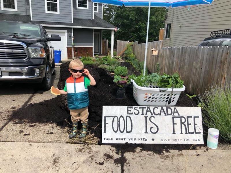 COURTESY PHOTO - Rhiannon Sundberg's son Wyatt shows off a few of the items available from the free community food pickup event in Estacada.