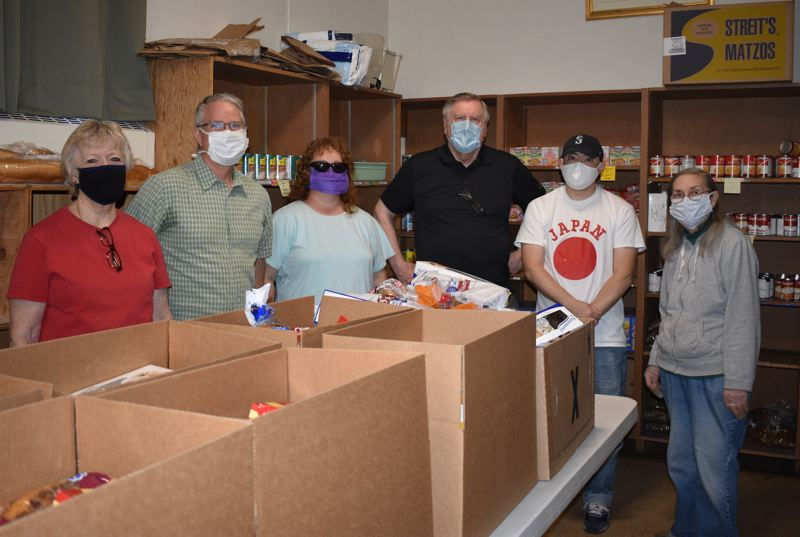 PMG PHOTO: TERESA CARSON - Volunteers at the St. Vincent de Paul food pantry at St. Henry Catholic Church momentarily break social distancing rules for a quick photo.