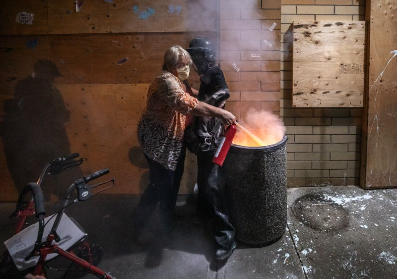 PMG PHOTO: JONATHAN HOUSE - A protester clad in black blocks a woman attempting to extinguish a trash fire set near the boarded-up front door of the East Precinct on Thursday, Aug. 6.