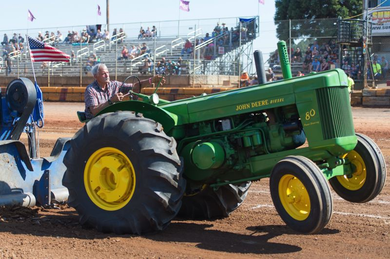 PMG FILE PHOTO - Ralph Puncochar of Hillsboro drives his John Deere tractor at Sunset Speedway during the Banks BBQ in 2018. The local Sunset Auto Parts, also known as Banks NAPA, has sponsored the event in the past.