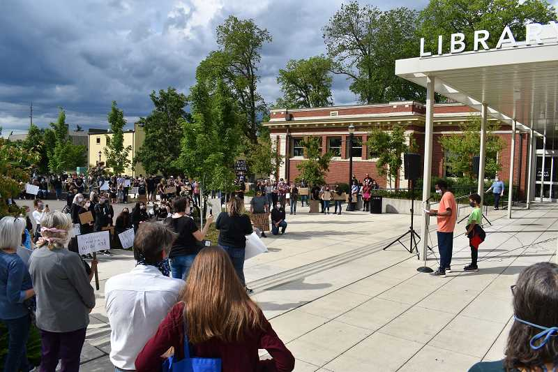 PMG PHOTO: RAYMOND RENDLEMAN - Tory Blackwell, a science teacher at Clackamas Community College, reads a poem during a June 5 protest at Oregon City's Library Park.