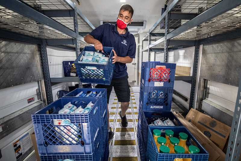 PMG PHOTO: JONATHAN HOUSE - Alpenrose milkman John Keller stacks boxes of milk for home delivery to customers.