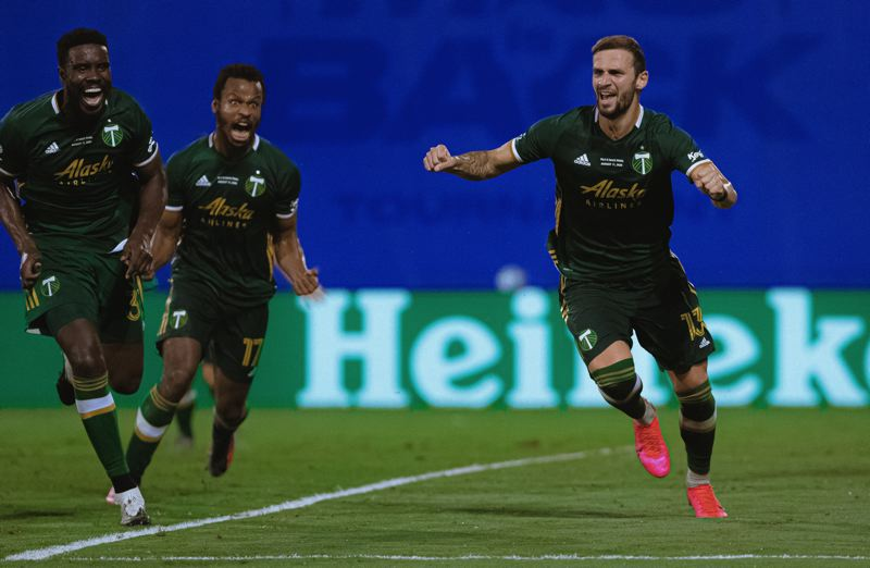 COURTESY PHOTO: JARED MARTINEZ/MLS/ADIDAS CREATORS NETWORK - Dario Zuparic (13), Larrys Mabiala and Jeremy Ebobissa (17) react after Zuparic scored the go-ahead goal in the Timbers' 2-1 win over Orlando City.