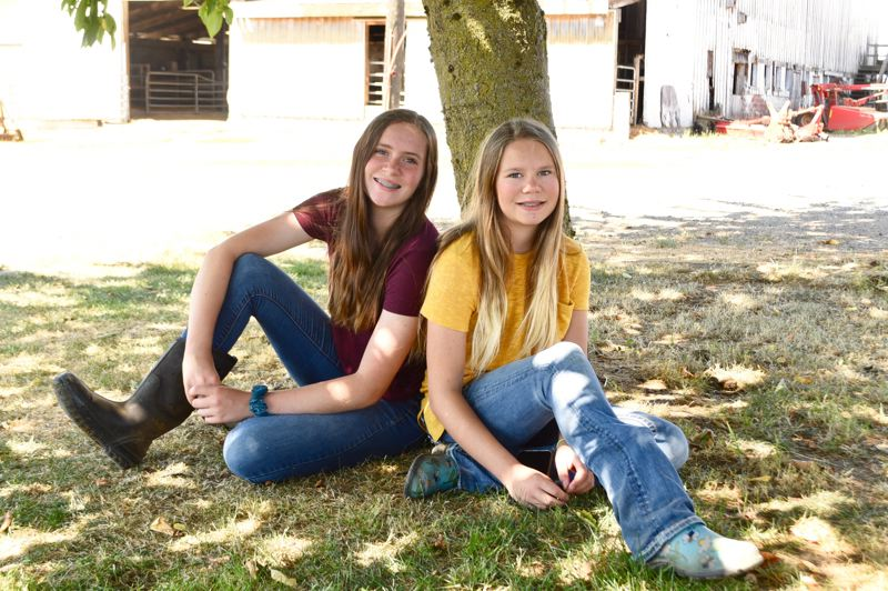 PMG PHOTO: BRITTANY ALLEN - Elizabeth, 15, and Autumn Collman, 12, both help work at their familys dairy farm in Boring when not doing homework, completing projects for 4-H or tending to numerous other responsibilities.