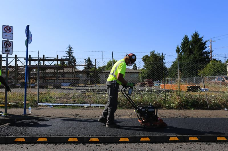 PHOTO: JOE YALOWITZ / PORTLAND BUREAU OF TRANSPORTATION - A bureau of transportation maintenance worker smooths out asphalt for a new temporary expanded TriMet bus stop at Southeast Washington Street and 80th Avenue on Wednesday, Aug. 5.