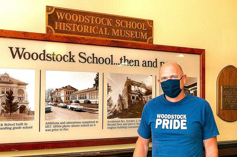 DAVID F. ASHTON - Woodstock Elementary School Principal Seth Johnson stands next to a Then and Now exhibit in his school - one that may eventually have to be updated to include the effects of the COVID-19 coronavirus.