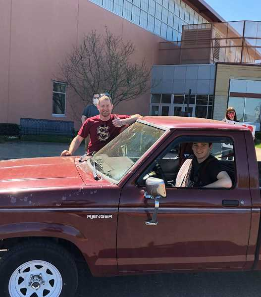 COURTESY PHOTO: ANDREW WACHSMUTH - Isaiah Wachsmuth drives through the graduation parade while his father, Andrew Wachsmuth, stands outside. The 17-year-old was excited to participate in the event.