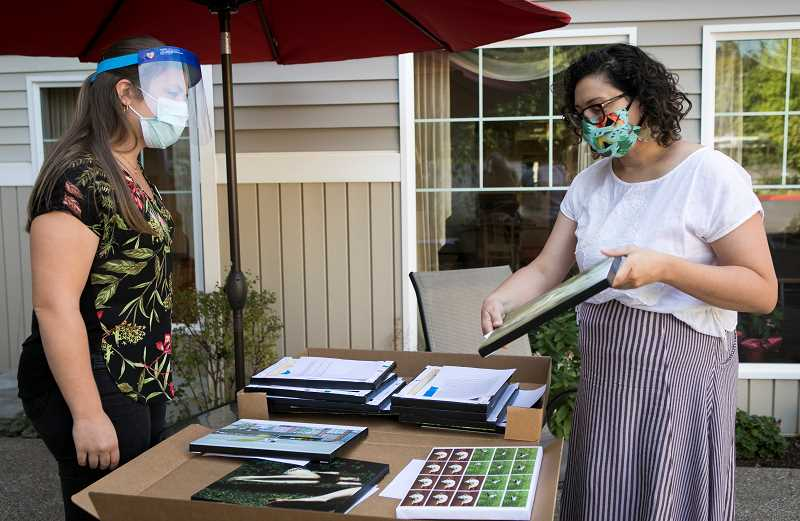 PMG PHOTO: JAIME VALDEZ - Zoe Wilson, left, activities director at Raleigh Hills Assisted Living, looks at the artwork created by artists for the residents at the facility presented by Kera Magarill, older adult behavior specialist with Washington County.