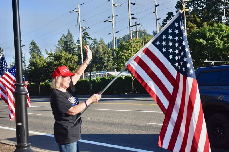 PMG PHOTO: EMILY LINDSTRAND - Juli Hager of Sandy Backs the Blue waved an American Flag during an event in Estacada on Tuesday, Aug. 18.