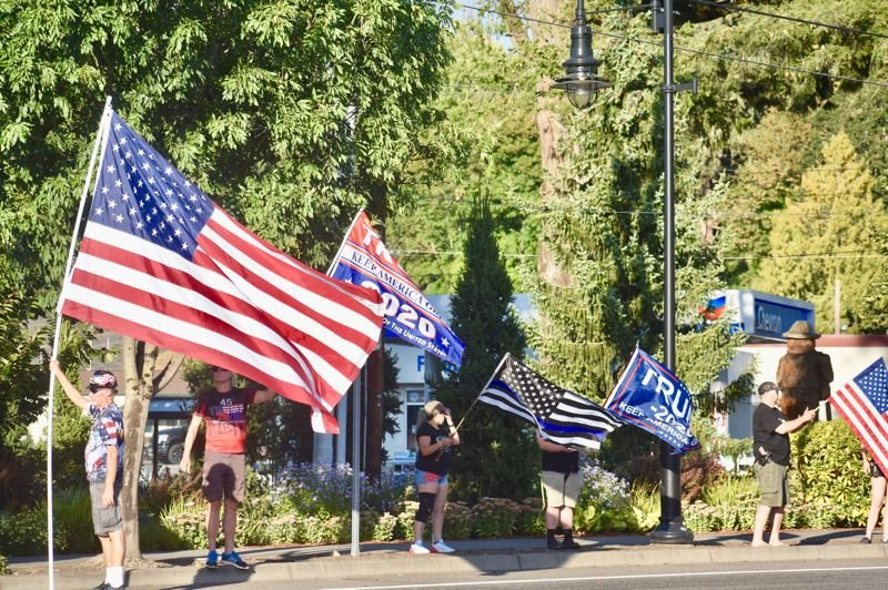 PMG PHOTO: EMILY LINDSTRAND - Participants in a flag wave gathered near Estacada City Hall on Tuesday, Aug. 18.