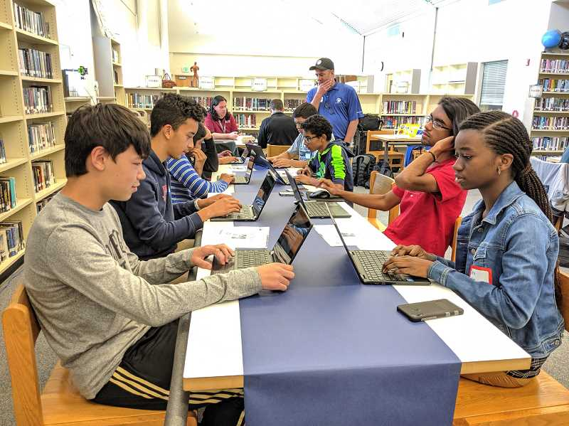 PMG FILE PHOTO - Westview High School students gather around a table for a coding competition. With help from Intel, the Beaverton Education Foundation hopes to continue connectivity for students at home.