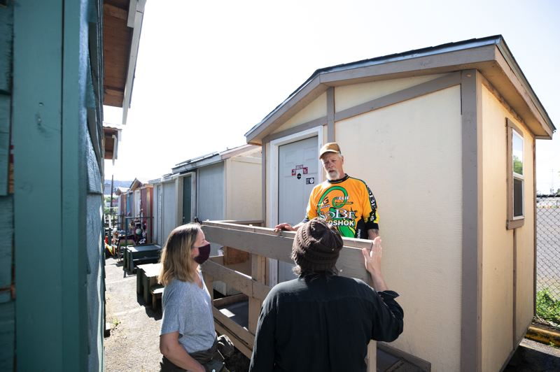 PMG PHOTO: JONATHAN HOUSE - Mack McKenzie talks to R2DToo board member Michael Moore and Lloyd EcoDistrict executive director Sarah Heinicke outside McKenzie's tiny home at Right 2 Dream Too.
