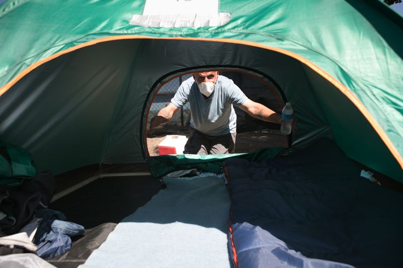 PMG PHOTO: JAIME VALDEZ - Russell, born and raised in Hillsboro, shows how he placed a frame along the edges of his tent to keep it flat at Safe Sleep Village.