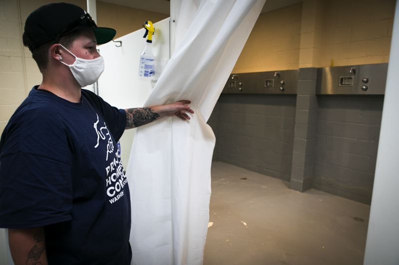 PMG PHOTO: JAIME VALDEZ - Amanda Terpening, services coordinator at Safe Sleep Village, shows the shower facilites at a county building near the homeless camp, which she says are santized fruequently to limit the risk of COVID-19 spreading.