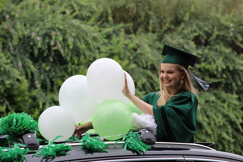PMG PHOTO: COURTNEY VAUGHN - Wilson High School graduate Trinity Harris adjusts balloons while waving for photos during a drive-thru graduation ceremony June 8. Starting in 2021, some high school seniors will have the option to purchase a more environmentally friendly graduation gown.