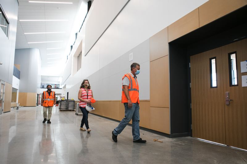 PMG PHOTO: JAIME VALDEZ - From left, Jane Siguenza, Hillsboro School District bond marketing specialist; Emily Caldwell Brookwood Elementary School principal; and Adam Stewart, capital projects officer, walk through the halls of the newly constructed Brookwood Elementary School.